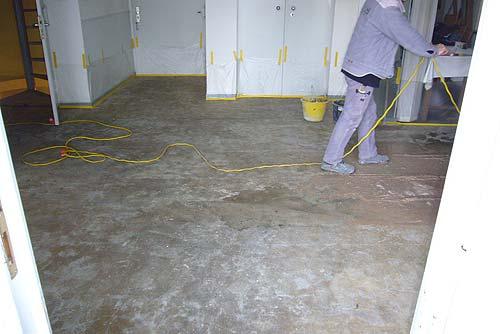 Ein Betonwerksteinboden nach Entfernen des Teppichbelags mit starken Kleberresten