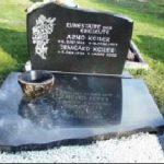 Grabmal aus scharzem Granit mit Abdeckplatte und Blumenornament