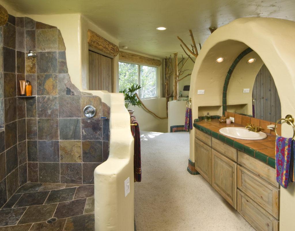 Die organischen Wände des Badezimmers sind mit Tadelakt verkleidet, dazu Buntschiefer in der offenen Dusche.