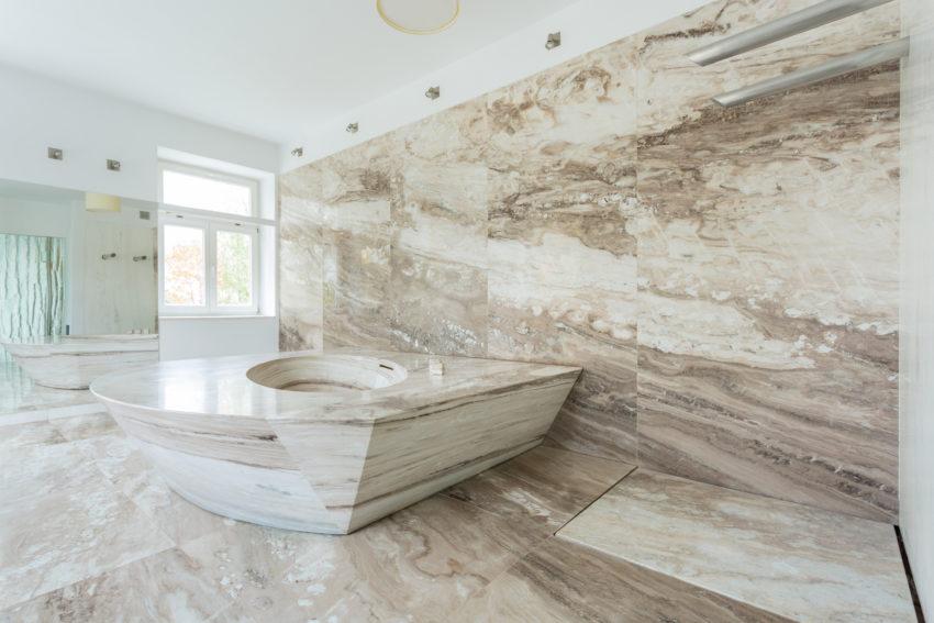 Großzügiges Badezimmer, ausgekleidet mit beigem Marmor. Highlight ist die massive marmorne Badewanne.