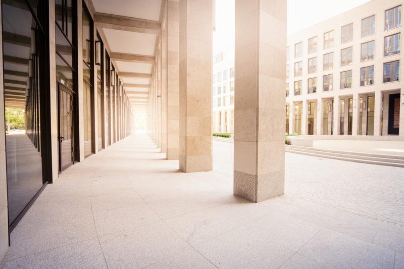 Fassaden- und Pfeilerverkleidung aus hellem Kalkstein.