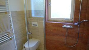 Für die Badezimmergestaltung wurden Akzente aus wunderschönem roten Travertin in Dusche und am Boden gesetzt, ergänzt von zeitlos schönem beigem Travertin.
