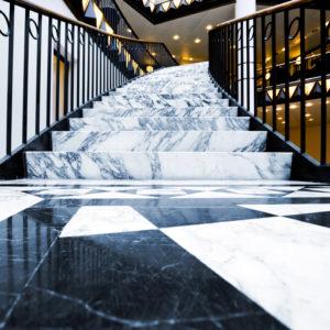 Helle Marmortreppe mit dunkler Maserung und schwarz-weißem Marmorboden.