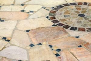 Mosaikboden aus größeren, beigen Naturstein-Polygonalplatten und bunten Mosaiksteinen