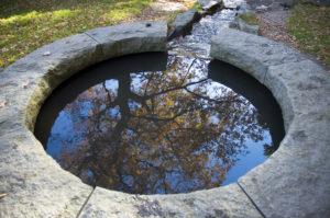 Kleiner Gartenteich mit grob behauener Natursteineinfassung, der in einem kleinen Bachlauf endet.