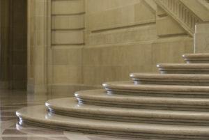 Eine Treppe aus beigem, polierten Naturstein mit runden Stufen und aufwändig profilierten Vorderkanten.