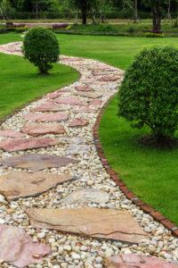 Gartenpfad aus rot-beigen Steinplatten und Kies