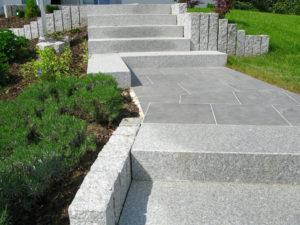 Treppe durch den Garten aus massiven grauen Granitstufen samt Plattenbelag auf dem Weg und Beetbegrenzung
