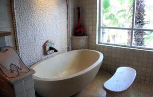 Edle Badewanne, umrahmt von einem beigen Kalksteinfußboden, weißen Kieseln als Wandbelag und Mosaikverzierungen