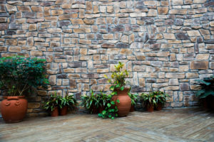 Mauerwerk aus bräunlichem Naturstein in unregelmäßigem Schichtenverband mit dunklen Fugen.