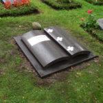 Liegeplatte in Form eines abstrakten Buches aus Basalt mit Edelstahlintarsien