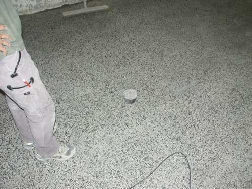 Der Boden wurde vorgeschliffen. Um die Farbe für den neuen Terrazzo zu ermitteln wurden in der Werkstatt Muster angelegt, die nun mit dem vorhandenen Boden verglichen werden.