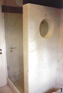 Gemauerte Duschabtrennung aus den 50iger Jahren, durch ein rundes Fenster optisch aufgelockert und mit Marmor verkleidet