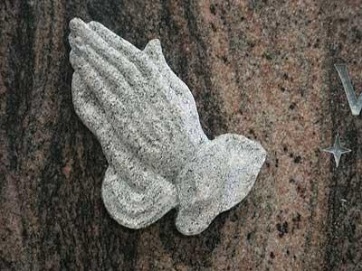 Erhaben-plastische betende Hände auf einem polierten Grabstein.