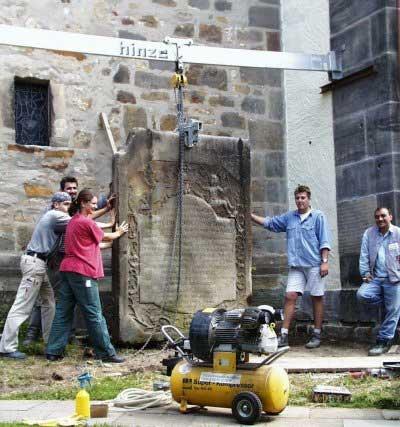 Ein Teil unserer Belegschaft versetzt vorsichtig einen wertvollen historischen Epitaph, nachdem dieser restauriert wurde.