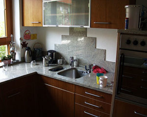 Küchenarbeitsplatte aus grauem Granit mit individueller Rückwand aus Natursteinfliesen