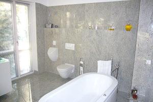 Badezimmer aus grauem Gneiss mit freistehender Badewanne