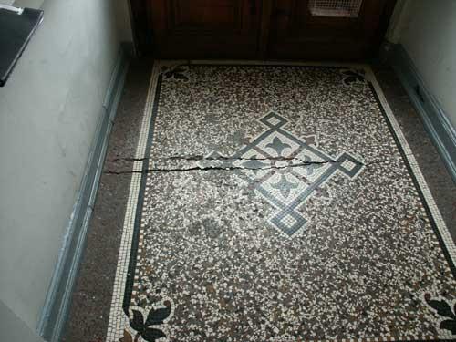 Der mit aufwändigem Mosaik und Friesen verzierte Eingang eines Bürgerhauses ist stark beschädigt, das Mosaik droht ganz zerstört zu werden.