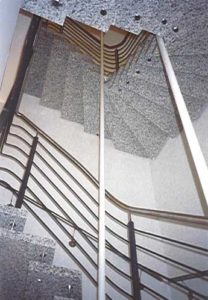 Freitragende Bolzentreppe aus grauem Granit über drei Geschosse in einem Bürogebäude