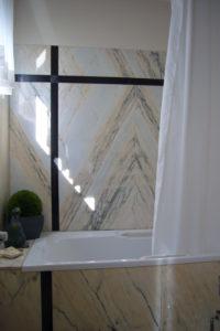 Die weiß-beigen Marmorfliesen an den Wänden des Bades wurden spiegelsymmetrisch kombiniert, schwarzer Marmor setzt Akzente.