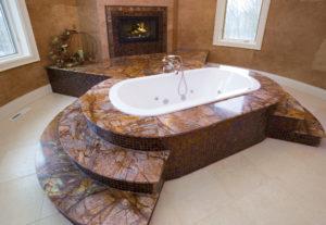 Exklusive Badewanne aus rötlichem Quarzit mit bunt schillernden Adern, dazu Mosaik in rotbraun.