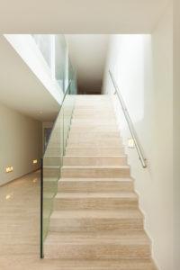Treppe aus beigem, polierten Marmor, kombiniert mit einer Seitenwand aus Glas
