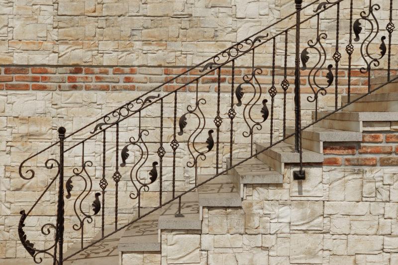 Treppe aus Sandstein und Fassade mit Sandsteinverkleidung und Klinkerfries, dazu ein schmiedeeisernes Geländer