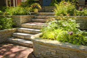 Trockenmauern um Hochbeete,dazwischen eine Gartentreppe. Beides aus beigem Sandstein.