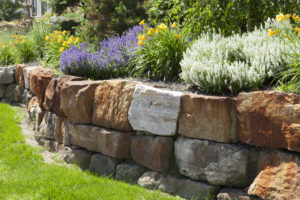 Wunderschöne Trockenmauer aus rötlichem Naturstein um ein Hochbeet