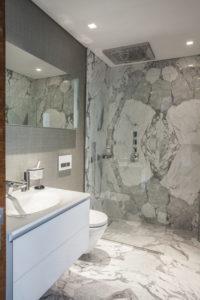 Badezimmer mit hochwertigem grau-weißen Marmor an Wänden und Boden.
