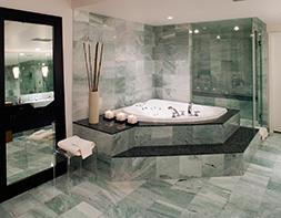 Badezimmer, in dem grüner und schwarzer Naturstein wunderschön kombiniert wurden.