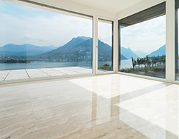 Bodenbelag aus hellbeigen, polierten Natursteinplatten.