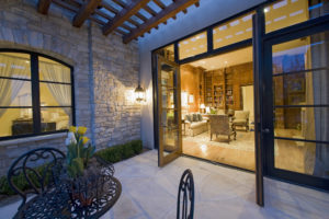 Terrasse mit großformatigem Natursteinboden und dazu passender Mauerverkleidung aus bruchrauem hellen Sandstein.