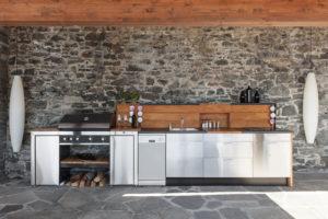 Grill, Waschbecken, Spülmaschine und Kochplatten kombiniert in einer modernen Outdoorküche mit Natursteinplatte.