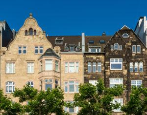 Neben dem Neubau von Fassaden aller Art sanieren auch alte. Hier der Vergleich eines restaurierten Hauses neben einer verschwärzten Sandsteinfassade.
