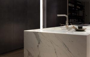Massiv wirkender Küchenblock aus weißem Marmor mit grauen Adern