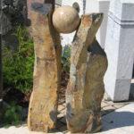 Zwei Basaltsäulen tragen eine polierte Granitkugel. Inschriften können in beide Stelen eingehauen werden.
