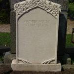 Grabmal aus beigem Sandstein mit umlaufender Rosenranke, die eine Art Dach bildet.
