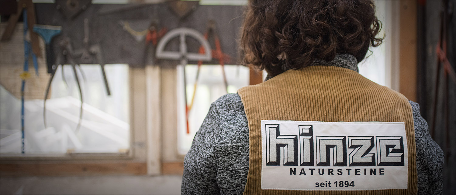 Ein Steinmetz steht vor einer Werkbank mit traditionellen Werkzeugen. Zu sehen ist das Logo der Steinhauerei Hinze auf dem Rücken des Steinmetzes.